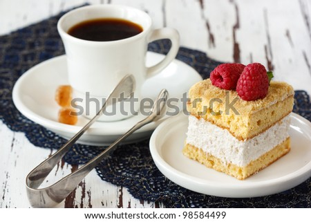 Delicious cake with fresh raspberries and cup of coffee.