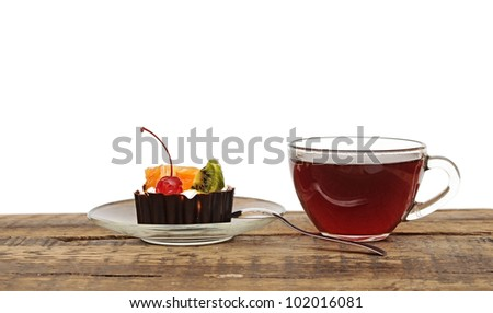delicious cake with fruit and a cup of tea - stock photo