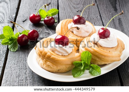 Delicious cakes of choux pastry with cream and cherries. Ripe cherries and mint on a dark wooden table - stock photo