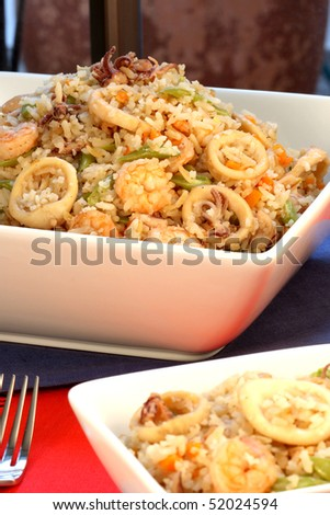 delicious calamary rice with assorted seafood and vegetables served on nice fancy table