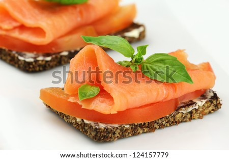 Delicious canape with smoked salmon, tomatoes and fresh basil - stock photo