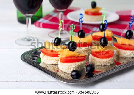 delicious canapes on iron dressing on a white wooden background near the wineglasses with wine - stock photo