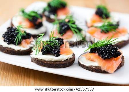Delicious canapes with salmon and caviar - stock photo