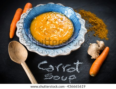 delicious carrot soup with ginger over slate background
