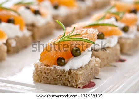 delicious catering finger food set with smoked salmon and rosemary - stock photo