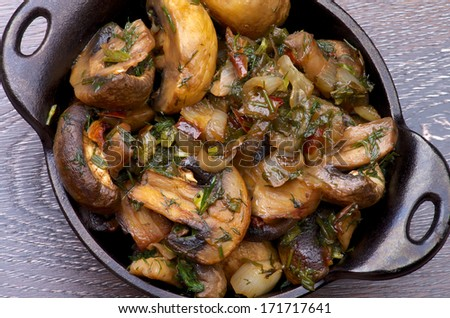 Delicious Champignon Mushrooms Stew with Onion and Greens in Black Cast-iron Stew Pot on Wooden background - stock photo