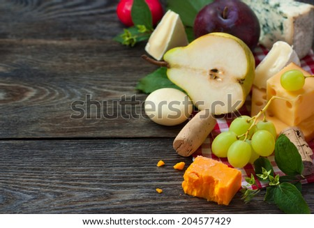 Delicious cheese and fruits on a wooden board. Food ingredients background. Selective focus. - stock photo