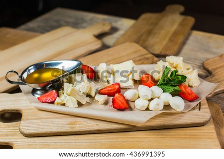 Delicious Cheese heaven. Cheese Mix, gouda cheese, cheese parmesan, feta cheese and strawberries with sauce on a wooden board - stock photo