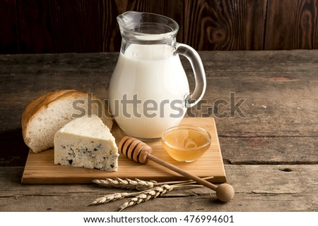 Delicious cheese, honey,bread and jug of milk on wooden cooking board. Copy space.