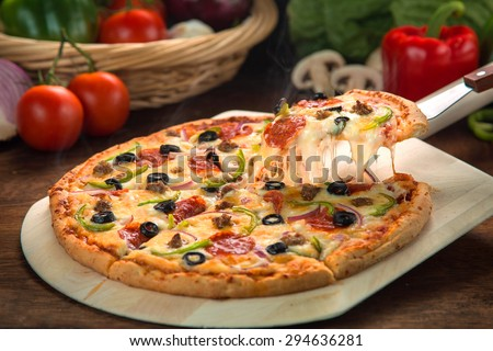 Delicious cheese stringy slice lifted of full supreme pizza baked fresh out of the oven next to ingredients - stock photo