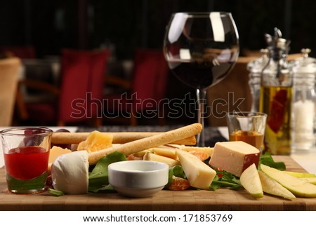 Delicious cheese wood plate with red wine