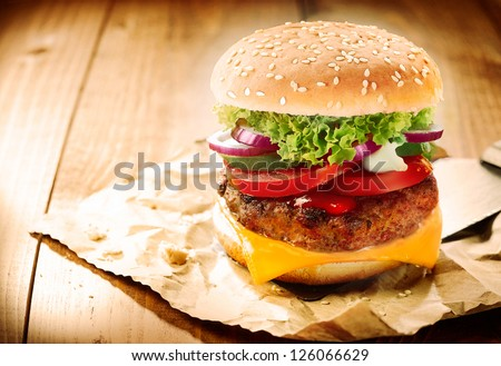 Delicious cheeseburger stacked high with a juicy beef patty, cheese, fresh lettuce, onion and tomato on a fresh bun with sesame seed standing on brown paper on a wooden tabletop with copyspace - stock photo