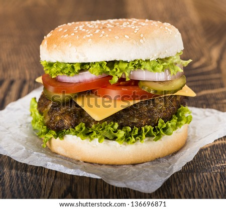 Delicious cheeseburger with a juicy beef, cheese, fresh lettuce, onion, pickle and tomato on a sesame seed bun photographed on a baking paper on a wooden table - stock photo
