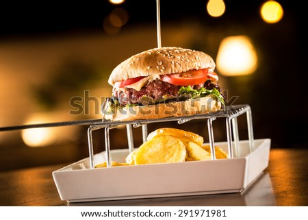 Delicious cheeseburger with fried potatoes in a restaurant. - stock photo