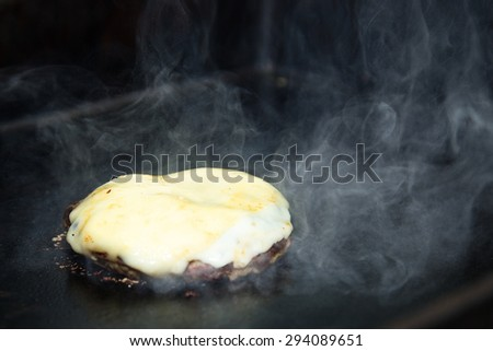 Delicious Cheeseburgers With a slice of fresh cheese melting on top of it On Barbecue - stock photo