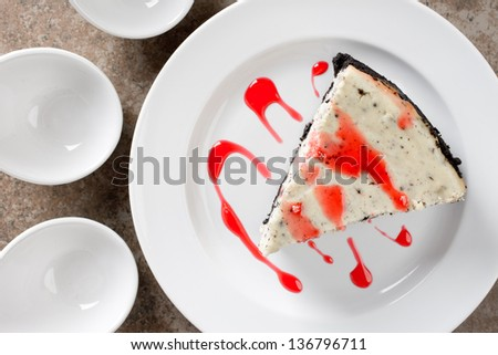Delicious Cheesecake with Chocolate Cookie Crust and Filling with Strawberry Syrup Drizzled on Top (Top View) - stock photo