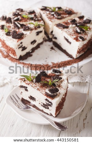 Delicious cheesecake with chocolate cookies closeup on a plate. vertical