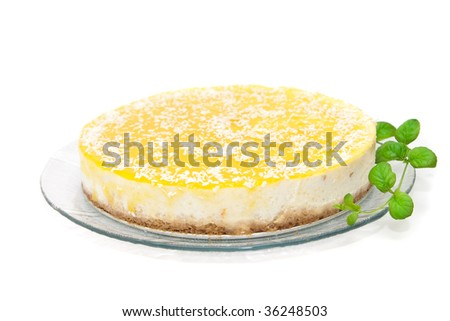 Delicious cheesecake with mango decorated with mint isolated on white - stock photo
