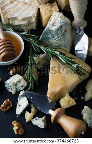 Delicious cheeses on a board with honey, nuts and wine on a dark background - stock photo