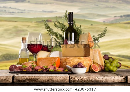 Delicious cheeses with red wine on wooden table. Italian countryside, Tuscany. - stock photo