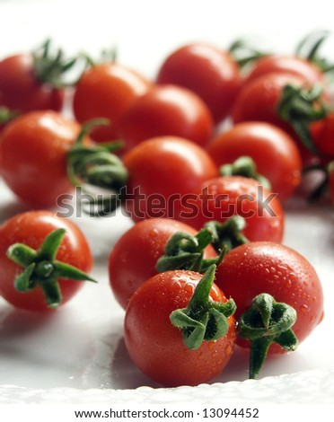 Delicious cherry tomatoes on a white plate - stock photo