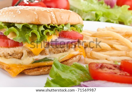 delicious chicken cheeseburger with melted cheddar cheese, french fries and ingredients - stock photo