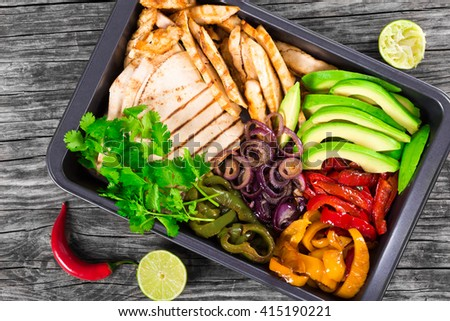 Delicious Chicken Fajita Platter with Avocado, Lime, Pita bread, Bell Pepper, Red Onion and Cilantro, close up, top view - stock photo