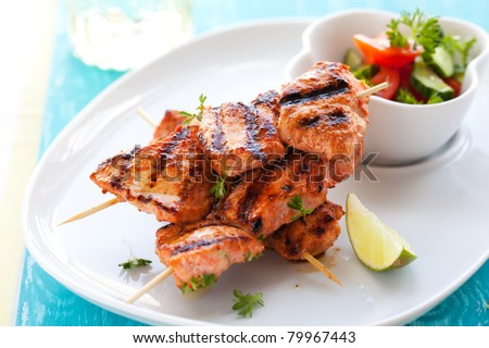 Delicious chicken masala skewers with vegetable salad. - stock photo