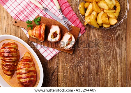 Delicious chicken rolls with dried tomatoes and mozzarella, served with roasted potatoes. - stock photo