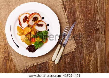 Delicious chicken rolls with dried tomatoes and mozzarella, served with vegetables and roasted potatoes. - stock photo