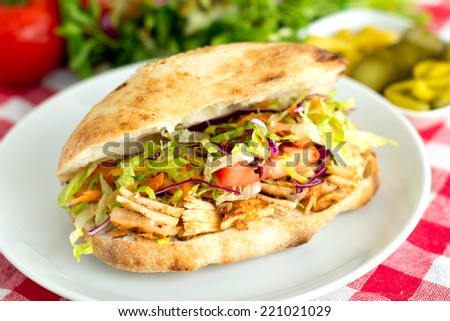 Delicious chicken sandwich doner kebab with some raw vegetables served on a table.  - stock photo
