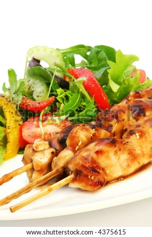Delicious chicken satay skewers with fresh green salad. - stock photo