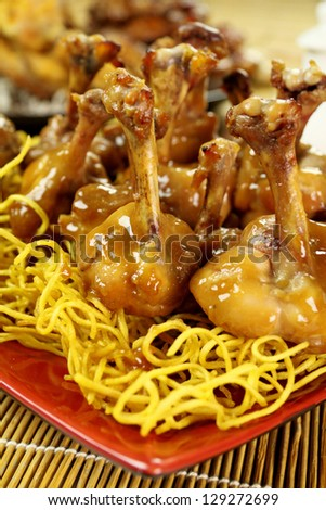 Delicious Chinese chicken drumettes on a bed of noodles.