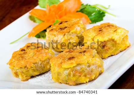 Delicious Chinese Dim Sum cakes grilled and served on a plate with a carrot garnish. - stock photo