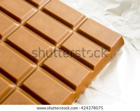 delicious chocolate bar on foil packaging - stock photo
