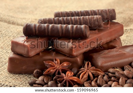 Delicious chocolate bars with coffee beans on sackcloth background - stock photo