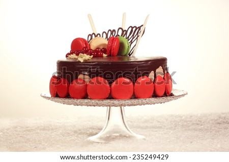 Delicious chocolate cake decorated with red and green macaroons - stock photo