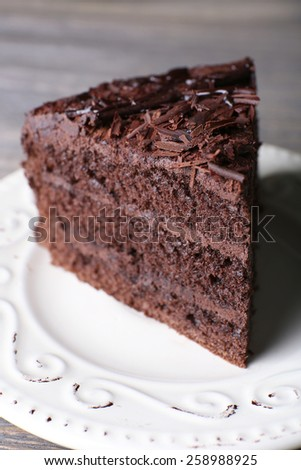 Delicious chocolate cake in white plate on wooden table background, closeup - stock photo