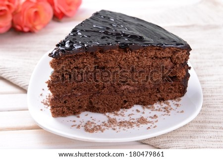 Delicious chocolate cake on plate on table close-up - stock photo