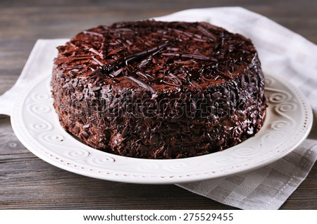 Delicious chocolate cake on plate with napkin on wooden table background - stock photo