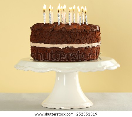 Delicious chocolate cake with candles on table on beige background - stock photo