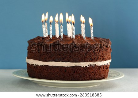 Delicious chocolate cake with candles on table on blue background - stock photo