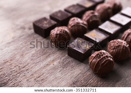 Delicious chocolate candies on wooden background - stock photo
