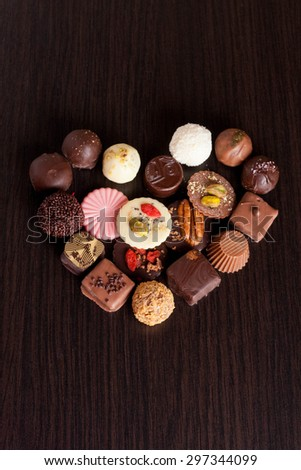 Delicious chocolate candies on wooden background, vertical - stock photo