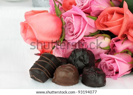 Delicious chocolate candies with a bouquet of roses. - stock photo