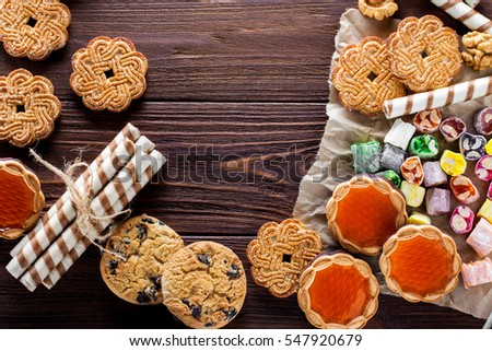 delicious chocolate chip cookies, cookies with sugar, wafer rolls on an old wooden table. horizontal view from above.