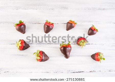 delicious chocolate covered strawberries on an old wooden background - stock photo