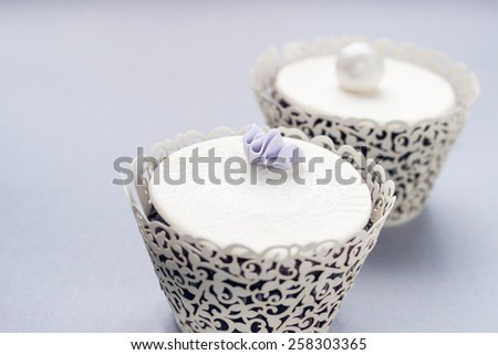 Delicious chocolate cupcakes decorated with lace made in fondant. Perfect for a delicate, pastel color palette of a whimsical vintage wedding. Selective focus with subtle toning and grain applied. - stock photo