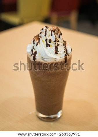 Delicious chocolate frappe with whipped cream on table