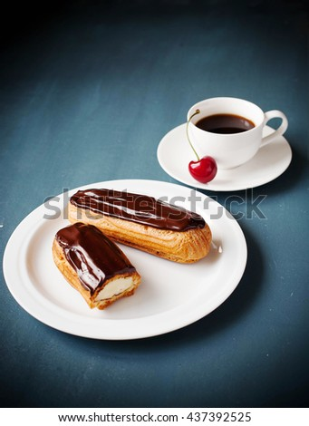 Delicious chocolate glazed french eclair filled with pastry cream, served with coffee and cherries. Cut in half eclair. Close up view, Dark background. - stock photo